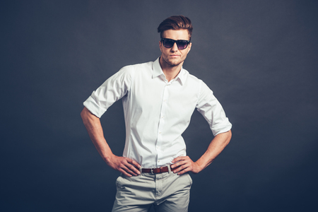 arms akimbo: How you doing? Confident young handsome man in sunglasses keeping arms akimbo and looking at camera while standing against grey background