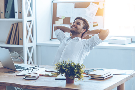 people from behind: Great job. Cheerful young handsome man keeping hands behind his head and looking away with smile while sitting at his working place