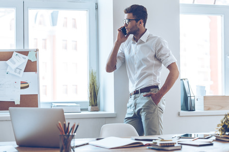 business in hand: BUsiness talk. Handsome young man in glasses talking on mobile phone and looking through window while standing in office