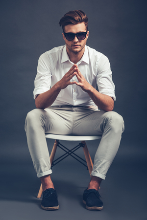 man sit: Mr Cool. Full length of confident young handsome man in sunglasses keeping hands clasped and looking at camera while sitting in chair against grey background Stock Photo