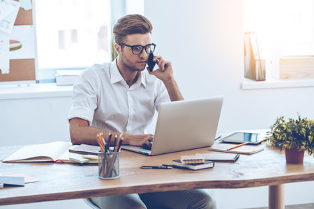business man phone: Let me check my timetable! Young handsome man using his laptop and talking on mobile phone while sitting at his working place Stock Photo