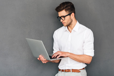 man with laptop: Checking his timetable. Confident young man holding laptop and typing while standing against grey background