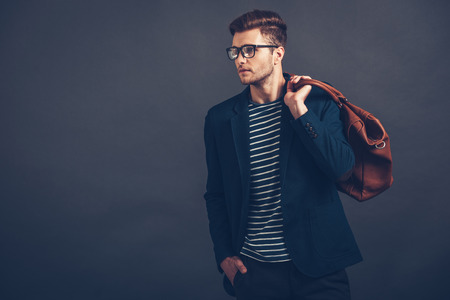 Styled for new day. Confident young handsome man in glasses holding bag and looking away while standing against grey background