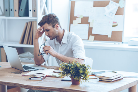 office manager: Feeling tired. Frustrated young handsome man looking exhausted while sitting at his working place and carrying his glasses in hand Stock Photo