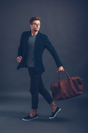 walk in: Style in action. Full length of confident young handsome man in glasses carrying bag and looking away while walking against grey background
