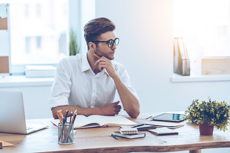 Thinking about solution. Pensive young handsome man keeping hand on chin and looking away while sitting at his working place Stock Photo