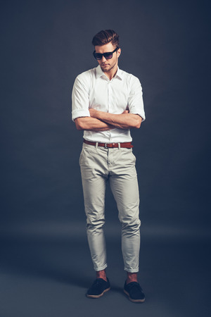 Casually handsome. Full length of confident young handsome man in sunglasses keeping arms crossed and looking down while standing against grey background