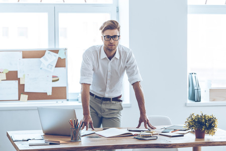 office manager: Real manager. Handsome young man in glasses looking at camera while leaning to the table in office Stock Photo