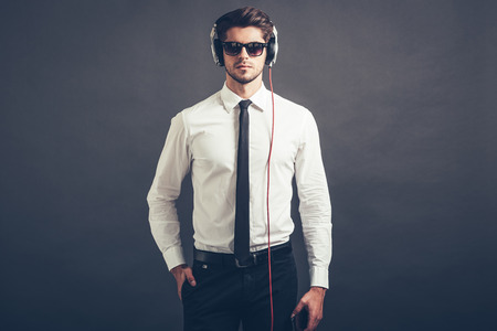 welldressed: Music is his style. Handsome well-dressed young man in headphones looking at camera while standing against grey background