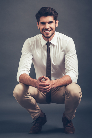 crouched: Elegant and cheerful. Full length of confident young handsome man looking at camera with smile while sitting crouched against grey background