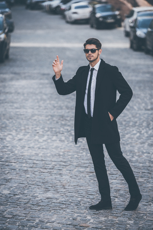welldressed: Hey taxi! Full length of handsome young well-dressed man in sunglasses waving for taxi while walking outdoors Stock Photo