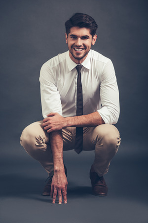 crouched: Can you resist his smile? Full length of confident young handsome man looking at camera with smile while sitting crouched against grey background Stock Photo