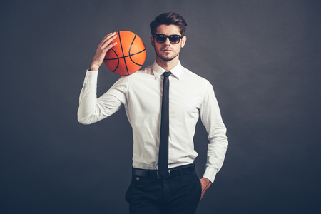 man shirt: Playing by his own rules. Handsome young man in shirt and tie holding basketball ball on his shoulder and looking at camera while standing against grey background