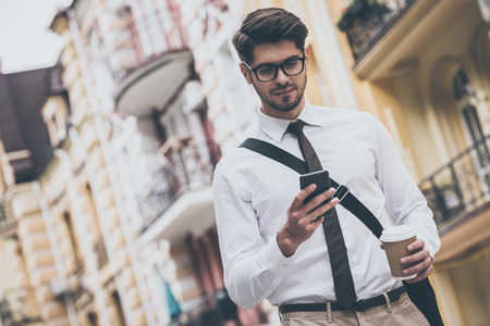 to go cup: Coffee break on a go. Low angle view of confident young man in glasses holding coffee cup and using his smart phone while walking outdoors