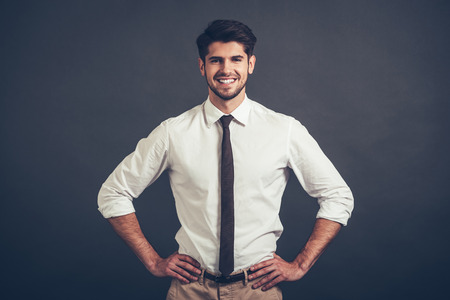 arms akimbo: Best smile. Confident young handsome man keeping arms akimbo and looking at camera with smile while standing against grey background
