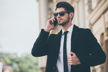 welldressed: Important call. Handsome young well-dressed man in sunglasses talking on mobile phone and looking away while standing outdoors