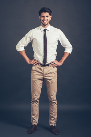 arms akimbo: Keep smiling. Full length of confident young handsome man keeping arms akimbo and looking at camera with smile while standing against grey background