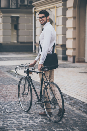 casual office: Getting to work. Rear view of cheerful young man in glasses looking at camera with smile and holding hand on his bicycle while standing outdoors Stock Photo