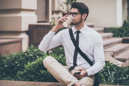 legs crossed on knee: Sip of fresh coffee before working day. Confident young man in glasses drinking coffee and holding his smart phone while sitting outdoors
