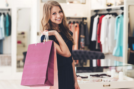 looking to camera: Satisfied with her shopping. Beautiful young woman with shopping bags looking at camera with smile while standing at the store