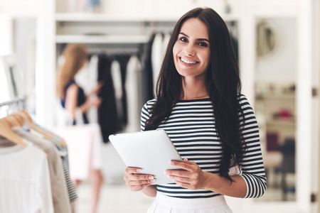 tienda de ropa: A partir de nuevos negocios. Joven y bella mujer que sostiene la tablilla digital y mirando a la cámara con sonrisa mientras se está en la tienda de ropa