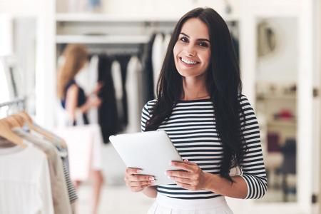 Nieuwe zaken beginnen. Mooie jonge vrouw die digitale tablet houdt en camera met glimlach bekijkt terwijl status bij de kledingsopslag