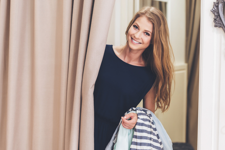 fitting room: Can you bring me on more dress please! Beautiful young woman holding clothing and looking at camera with smile while standing in fitting room at the store