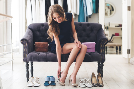 That is perfect pair! Beautiful young woman trying on high heel shoes while sitting on sofa at the shoe store Stockfoto