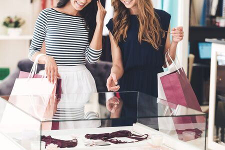 woman clothes: Maybe this is one? Close-up of two beautiful women with shopping bags looking at lingerie showcase with smile while standing at the store