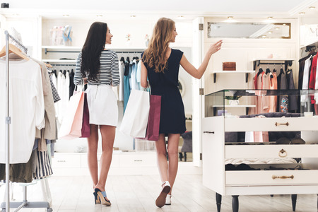We should look at new dresses! Rear view of two beautiful women with shopping bags looking away with smile while walking at the clothing store