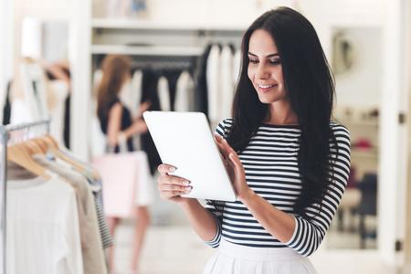 tienda de ropa: Tecnologías hacen negocio más fácil. mujer joven hermosa que usa su tableta digital con sonrisa mientras se está en la tienda de ropa