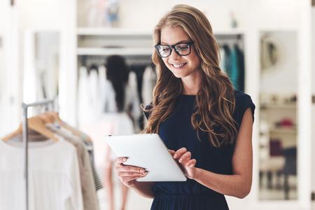 À partir de nouvelles affaires. Belle jeune femme utilisant tablette numérique avec le sourire tout en se tenant à la boutique de vêtements