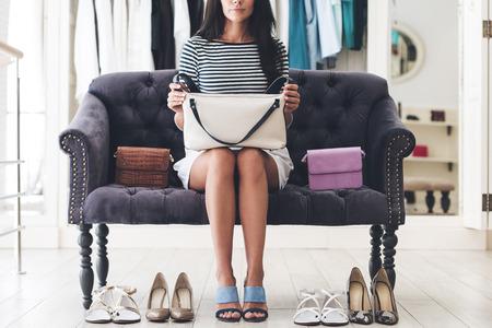 tienda zapatos: Difícil elegir el par perfecto. Parte del monedero de mujer joven linda celebración de cuero mientras se está sentado en el sofá en la tienda de zapatos Foto de archivo