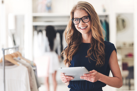 Modern businesswoman. Beautiful young woman holding digital tablet and looking at camera with smile while standing at the clothing store