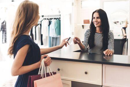 Kan ik met mijn kaart betalen? Mooie jonge vrouw met boodschappentassen die haar creditcard aan verkoper geven terwijl ze bij de kledingwinkel staan
