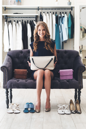 Perfect match is found! Beautiful young cheerful woman holding leather purse and looking at camera with smile while sitting on sofa at the clothing store