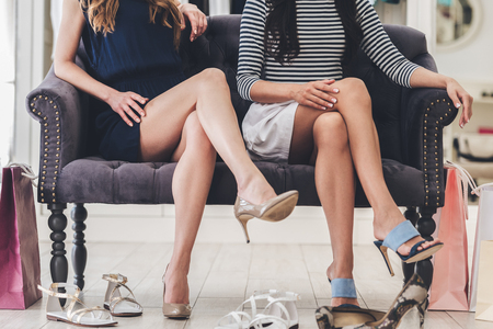 legs crossed at knee: Confident with their choice. Part of young women with perfect legs keeping their legs crossed at knee while sitting on sofa at the shoe store Stock Photo