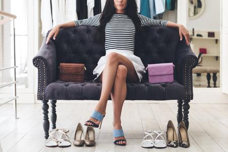shoe store: Segura de su elección. Parte de hermosas piernas de mujer joven manteniendo cruzados en la rodilla mientras está sentado en el sofá en la tienda de zapatos