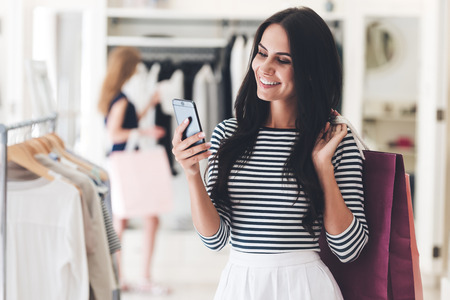 easier: Technologies make shopping easier. Beautiful young woman with shopping bags using her smart phone with smile while standing at the clothing store