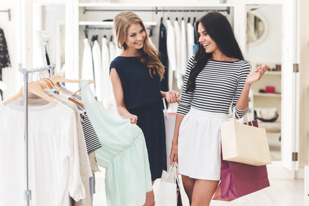 retail shopping: Maybe this dress? Two beautiful women with shopping bags looking at each other with smile while standing hear hanger at the clothing store