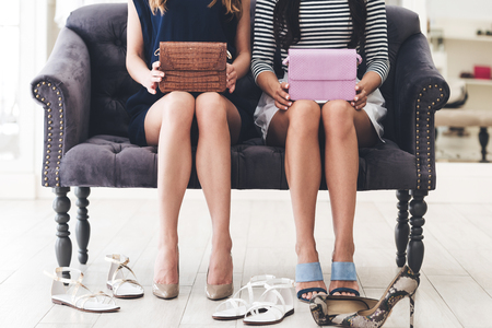 woman bag: At the retail store. CLose-up of young women with perfect legs holding leather purses while sitting on sofa at the shopping store Stock Photo