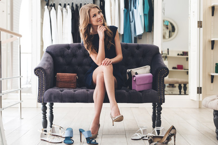 woman bag: Maybe I need another pair? Beautiful young woman looking thoughtful while sitting on sofa at the clothing store