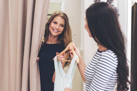 Você deve tentar sobre este vestido! Mulher nova bonita tomando vestido no cabide do vendedor em pé na sala de montagem na loja Banco de Imagens