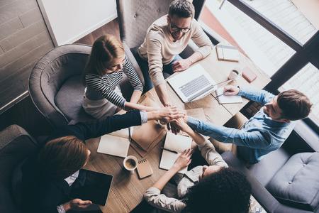 manos juntas: Equipo de éxito. Vista superior de jóvenes empresarios que llevan a cabo las manos mientras está sentado en la mesa de oficina junto Foto de archivo