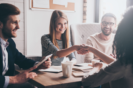 We have a deal! Two beautiful women shaking hands and looking at each other with smile while sitting at the business meeting with their coworkers Stockfoto