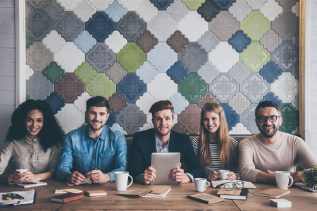 Dream team. Cheerful young people looking at camera with smile while sitting at the office table on business meeting Stockfoto