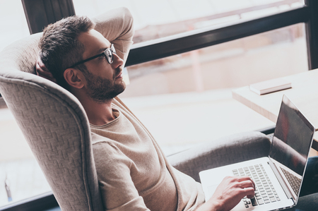 Searching for inspiration. Side view of handsome man using his laptop and looking pensive while sitting in chair in front of window Imagens