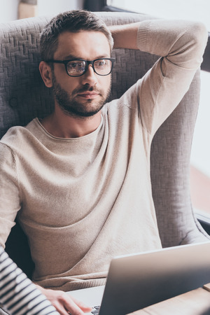 idea comfortable: Handsome and thoughtful. Handsome man using his laptop and looking pensive while sitting in chair Stock Photo