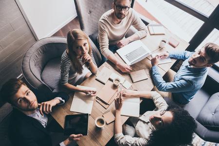 Sukces zespołu. Widok z góry na młodych ludzi biznesu patrząc na kamery, siedząc przy stole w biurze razem