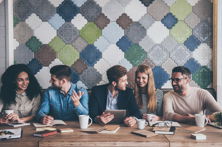 Skvělá obchodní jednání. Veselé mladé lidi, kteří se na sebe dívají s úsměvem a sedí u kancelářského stolu na schůzi Reklamní fotografie